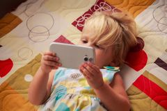 blonde girl plays with smartphone Royalty Free Stock Photography