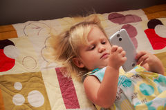 blonde girl plays with smartphone Royalty Free Stock Photos