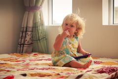 blonde girl plays with smartphone Stock Photography