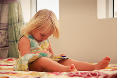 blonde girl plays with smartphone Royalty Free Stock Photo