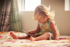 blonde girl plays with smartphone Royalty Free Stock Image