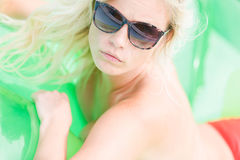 Blonde girl in pool. A blonde woman with sunglasses on an air mattress in a pool sun bathing