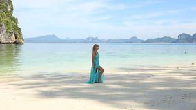 Blonde Girl Poses on Beach against Tranquil Transparent Azure Sea stock footage