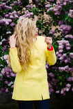 Blonde girl posing against blooming violet lilac tree. Portrait of blonde girl with wavy hair, posing and turned away and hiding face. Wearing yellow coat Royalty Free Stock Photo