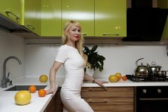 Blonde girl posing on camera standing in kitchen Royalty Free Stock Photos