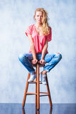 Blonde girl posing on a chair with legs wide open Royalty Free Stock Images