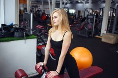 Blonde girl posing in the gym. She wears dark pants and black T-shirt. She relaxing and looking to window. Againstgym ball Stock Image