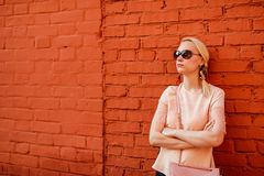Blonde girl posing near brick wall,pensive pose , sensual beauty face, dark glasses royalty free stock image