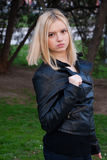 Blonde girl posing outdoors in leather jacket Stock Image
