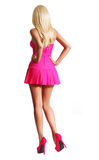 Blonde Girl Posing in Short Pink Dress and High Heels. On her Sexy Legs isolated on white, Backside. Barbie Doll Royalty Free Stock Image