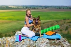 Blonde girl practices yoga with dogs, german shepherd Stock Photos