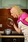 Blonde girl prepares food on kitchen Stock Photography