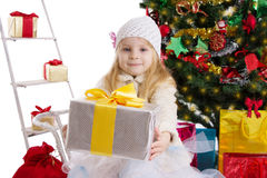 Blonde girl with present under Christmas tree royalty free stock image