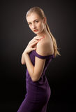 Blonde girl in purple dress Stock Images