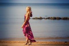 Blonde girl in purple dress walks on beach Royalty Free Stock Photo