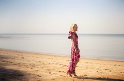Blonde girl in purple dress walks on beach Royalty Free Stock Photos