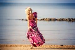 Blonde girl in purple dress walks on beach Stock Photos