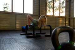 The blonde girl is push-up from the crossbeams installed on the royalty free stock photo