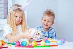 Blonde girl in rabbit ears on head and boy with little bunny. Colorful eggs and markers on table. Prepearing for Easter, family royalty free stock photos