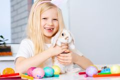 Blonde girl in rabbit ears on head and little bunny in her hands. Colorful eggs and markers on table. Prepearing for Easter and stock photo