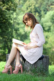Blonde girl reading a book in the park. Portrait of beautiful young blonde girl reading a book in the park stock photo