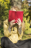 Blonde girl reading a book in a park on a sunny day. Blonde girl reading a red book in a park on a sunny autumn day Royalty Free Stock Image