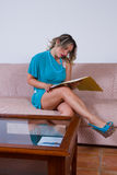 Blonde girl reading reports Royalty Free Stock Photography