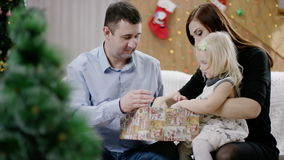 Blonde girl receiving christmas present by parents. Toddler unwrapping box with the present. happy family at christmas stock video