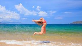 Blonde girl in red bikini jumps swings in shallow water. Blonde slim girl in red bikini jumps swings in shallow water wind shakes long hair against azure sea and stock footage