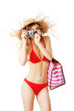 Blonde girl in red bikini is taking pictures. Isolated on white Royalty Free Stock Photos