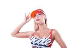 A blonde girl in a red cap with a transparent visor and a multicolour swimsuit holds on to the cap. Of a cap on a white background royalty free stock photography