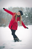 Blonde girl with red coat in winter snow Royalty Free Stock Photos