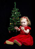 Blonde girl with red dress and christmas tree Stock Photos