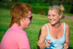 Blonde girl with red head cute boy in the pa. Blonde funny girl with red head cute boy in the park stock photo