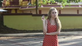 Blonde girl in a red polka-dot dress standing poses stock video footage