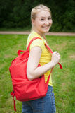 Blonde girl with red rucksack  in the park at summer Royalty Free Stock Photos