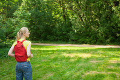 Blonde girl with red rucksack in the park at summer Stock Images