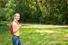 Blonde girl with red rucksack  in the park at summer Stock Image