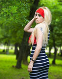 Blonde girl with red scarf and striped dress Stock Photos