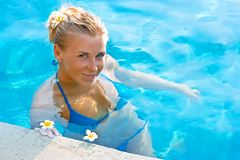 Blonde girl relaxing in hotel pool Stock Photos