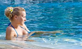 Blonde girl relaxing in hotel pool Royalty Free Stock Photos