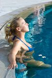 Blonde girl relaxing in hotel pool Royalty Free Stock Photo