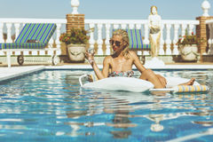 Blonde girl relaxing in pool Stock Image
