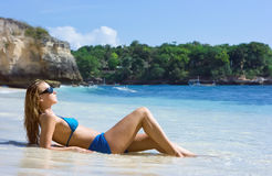 Blonde girl relaxing in water on the beach. On Bali island in Indonesia royalty free stock photo