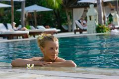 Blonde girl relaxing in water in the pool Royalty Free Stock Images