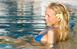 Blonde girl relaxing in water in the pool Royalty Free Stock Photography