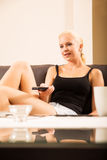 Blonde Girl with a remote control Royalty Free Stock Images