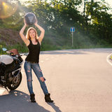 Blonde girl removes his helmet near motorcycle. Stock Image