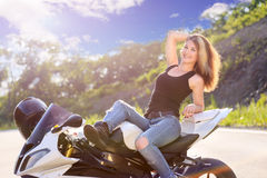 Blonde girl is resting in seat of modern motorcycle. Stock Photography