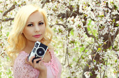 Blonde Girl with Retro Camera over Cherry Blossom. Beautiful Young Woman with Sakura. Spring Portret Stock Image